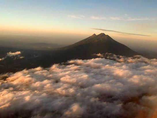 Pacaya Volcano rising thru the dust and clouds after takeoff from La Aurora Airport, Guatemala City, Guatemala. Photo by Barbara Guerra