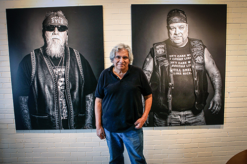 Moses Olmos poses in front of his work.